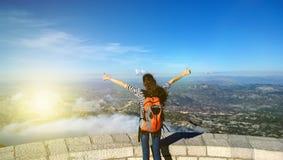 Brunettemädchen mit einem orange Rucksack, der auf einen Berg steht und die Ansicht betrachtet Stockfotografie