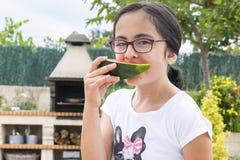 Brunettemädchen mit Gläsern Wassermelone essend Lizenzfreie Stockfotos