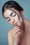 Brunettemädchen mit nasser Frisur der Mode und schönem Make-up auf blauem Hintergrund Schönes Baumuster mit perfektem Make-up Stockbild