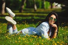 Brunettemädchen trägt ringsum Sonnenbrille, liegt auf grünem Gras des Sommers stockfotografie