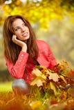 Brunettemädchen und goldene Blätter Lizenzfreies Stockfoto