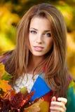 Brunettemädchen und goldene Blätter Stockfoto