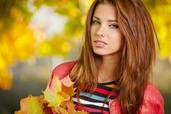 Brunettemädchen und goldene Blätter Stockbilder