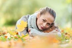 Brunettemädchen und goldene Blätter Lizenzfreie Stockfotografie