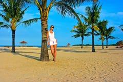 Brunettemädchen, das auf dem einsamen Sandstrand steht Lizenzfreie Stockfotos