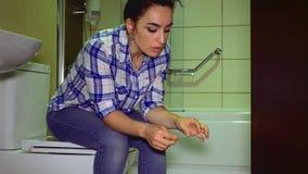 Brunetten en ung härlig student med ångest väntar på resultaten av en graviditetstest 4k stock video