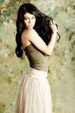 Brunetten för ung kvinna visar henne sunt hår Royaltyfri Bild