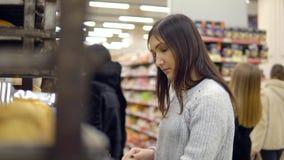 Brunetten i bagerivaruhuset väljer den nya bagetten stock video