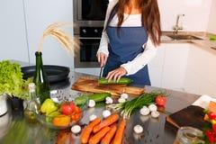 Brunetten i ett blått förkläde med hennes hår som är löst i köket, klipper en gurka royaltyfria foton