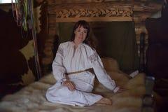 Brunetten i gammalmodig skjorta f?r vit linne med broderi sitter p? en medeltida s?ng arkivbilder