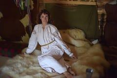Brunetten i gammalmodig skjorta f?r vit linne med broderi sitter p? en medeltida s?ng fotografering för bildbyråer