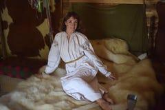 Brunetten i gammalmodig skjorta f?r vit linne med broderi sitter p? en medeltida s?ng royaltyfri foto