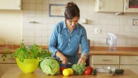 Brunetten i köket smular broccoli De flickadanserna och allsångerna till musik Hem- kök arkivfilmer