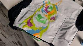Brunetten målar på ett grov bomullstvillomslag en illustration av en bull terrier ovanf?r sikt arkivfilmer