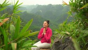 Brunetten sitter med de satta händerna tillsammans och ler Tacksamhet till naturen ler kvinnan grön dal stock video