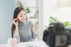Brunetten sitter på tabellen och lyssnar till musik på telefonen Hon gillar för att göra det Också är denna flicka fotografering för bildbyråer