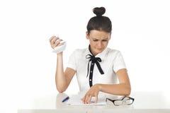 brunetten skrynklar att svära för skrivbordkontorspap Royaltyfria Foton