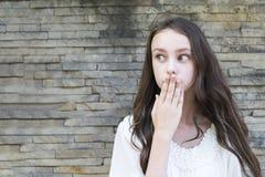 Brunetten täcker hennes mun fotografering för bildbyråer
