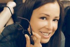 Brunetteportrait, Lesegläser in der Hand Stockfotos
