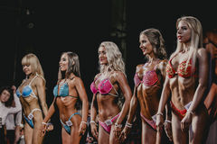 Brunettes and blondes athletes fitness bikinis show off their flat tummies Royalty Free Stock Photos