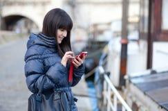 Brunettetourist beim Parissenden sms zu einem Franc Stockbilder