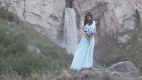Brunettflicka i en klänning på en vattenfallbakgrund arkivfilmer