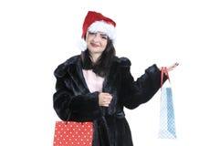 Brunettflicka i svart pälslag, i den santa hatten på isolerad bakgrundsståendejul som shoppar, försäljning Arkivbilder