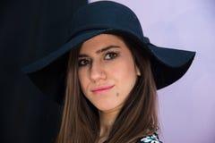 Brunettflicka med den långa hår och hatten, med tusenskönor för blom- klänning arkivfoto