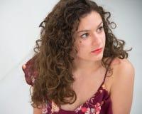 Brunettflicka med långt lockigt hår, med klänningen med tunna remmar, arkivbild