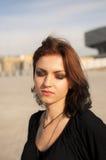 Brunettflicka med utomhus- rött hår Arkivfoto