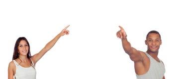Brunettflicka- och latinmän som pekar något Arkivbild