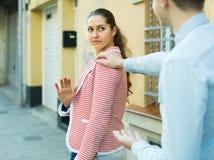 Brunettflicka som frågar mannen att stoppa besvära henne utomhus Arkivbild
