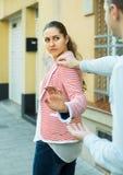 Brunettflicka som frågar mannen att stoppa besvära henne utomhus Fotografering för Bildbyråer