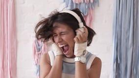 Brunettflicka som går galen, medan lyssna till musik i hennes hörlurar Skaka hennes huvud intensly och ropa ut högt lager videofilmer
