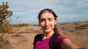 Brunettflicka som går på ett öde fält och tagande en selfie Handelsresande i Turkiet arkivfoton