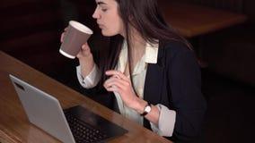Brunettflicka som har gyckel som pratar på en bärbar dator som ser eftertänksam och dricker kaffe i ett kafé lager videofilmer