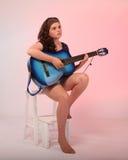 Brunettflicka som spelar den blåa gitarren Fotografering för Bildbyråer