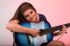 Brunettflicka som spelar den blåa gitarren Arkivfoton