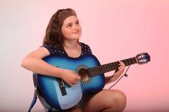 Brunettflicka som spelar den blåa gitarren Arkivbild