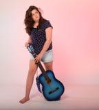 Brunettflicka som spelar den blåa gitarren Arkivfoto