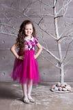 Brunettflickabarn 5 gamla år i en rosa klänning i feriegrå färgrum med trädet royaltyfri foto