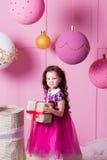 Brunettflickabarn 5 gamla år i en rosa klänning i rosa kvartsrum för ferie med gåvor arkivfoto