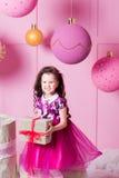 Brunettflickabarn 5 gamla år i en rosa klänning i rosa kvartsrum för ferie med gåvor royaltyfri foto