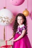 Brunettflickabarn 5 gamla år i en rosa klänning i rosa kvartsrum för ferie med gåvor arkivfoton