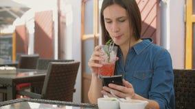 Brunettflickabruk ilar telefonen, medan sitta utanför i ett kafé, dricka och tycka om en kall drink från sugrörröret 4k, Arkivbilder