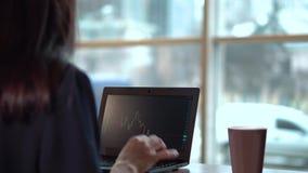 Brunettflickadrinkar kaffe och klockor som utbytet kartlägger på bärbara datorn lager videofilmer