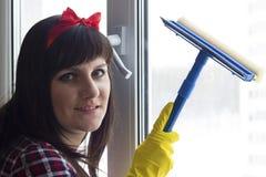 Brunettflickan i gula handskar tvättar fönstret arkivfoto