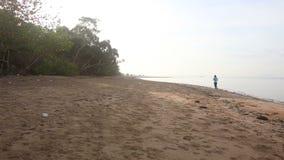 brunettflickan kör längs vattenkanten på gryning lager videofilmer