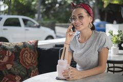 Brunettflickan sitter i gatakafé rymmer telefonen, modell i exponeringsglas med en telefon royaltyfri fotografi