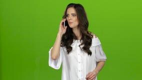 Brunettflickan svär på telefonen och skriker grön skärm arkivfilmer